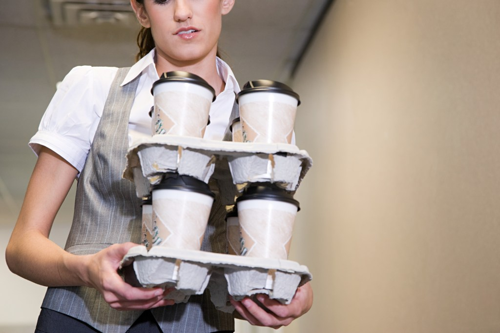 Woman carrying coffee cups --- Image by © Image Source/Corbis