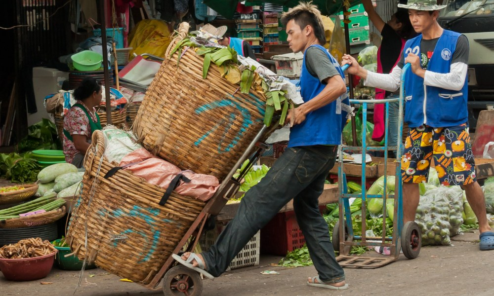 A porter prepares to wheel a load of vegetables from a delivery truck to a vendor at the Klong Toey Market in Bangkok, Thailand.  This large market provides fruit, vegetables, and meat to many restaurants, food cart vendors, and families in Bangkok.